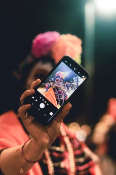 A woman in costume holds up a smartphone with a selfie she's just taken