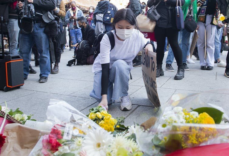A woman kneels down to place flowers at a memorial. Behind her, a protest.