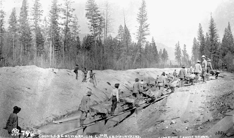 a black and white image of men working on the railway