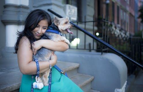 A woman hugs her dog.
