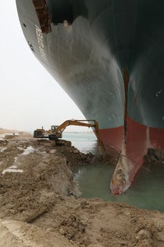 A digger extracting soil at the base of a large ship's hull