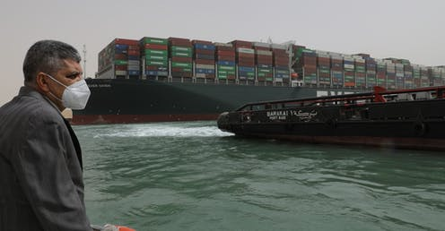 A man in a mask on a boat in fron tof the Ever Given container ship