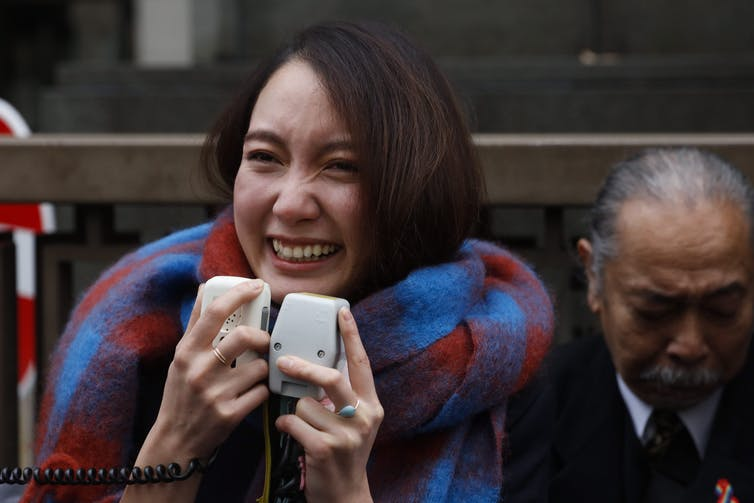 Woman stands smiling and crying while holding two microphones