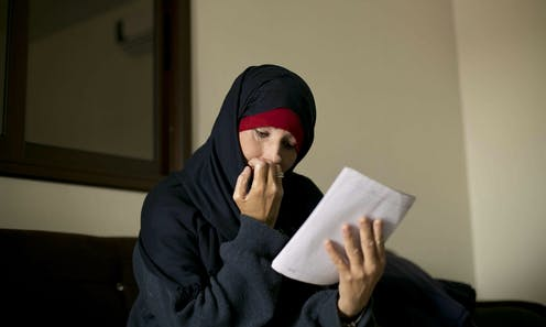 Woman wearing a hijab sits reading a letter