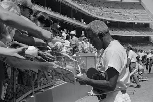 Jackie Robinson signing autographs.
