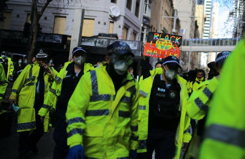 A group of police people in hi vis gear, walking in the street. There is a Black Lives Matter protest sign in the background.