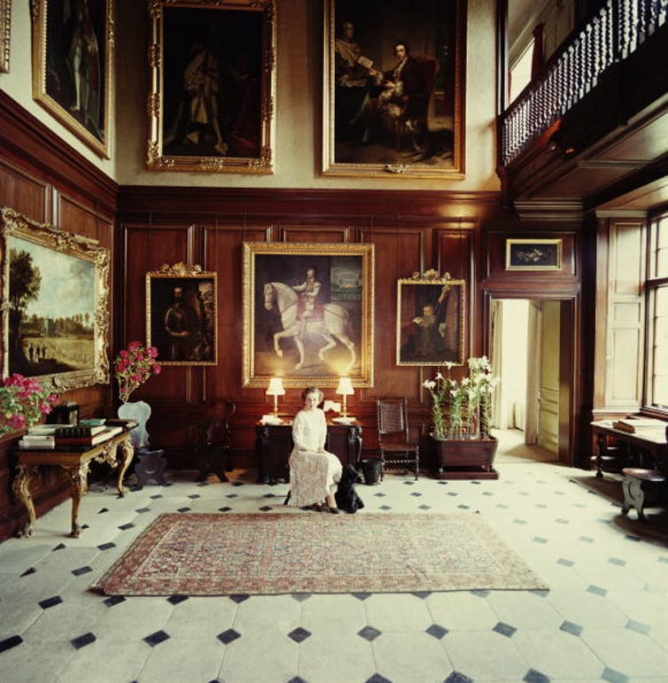 A woman in a grand room, surrounded by paintings.