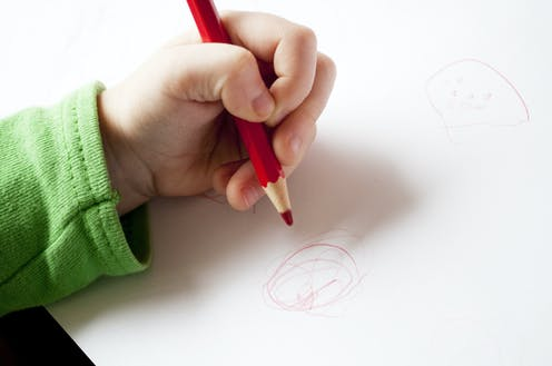 Child drawing with their left hand