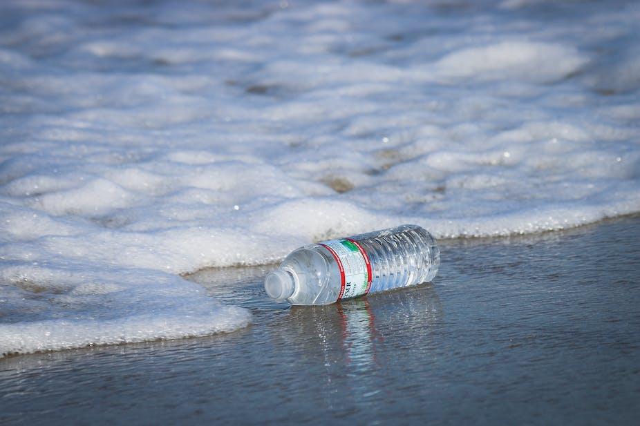 Botol air plastik terkena ombak di pantai.