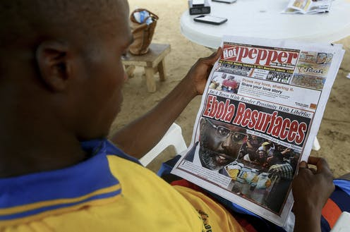 A Liberian man reads a newspaper reporting on the Ebola outbreak in neighbouring Guinea at a sidewalk news stand in Monrovia, Liberia.
