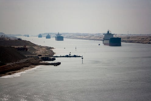 Cargo ships in single file moving along a narrow body of water between sandy banks.