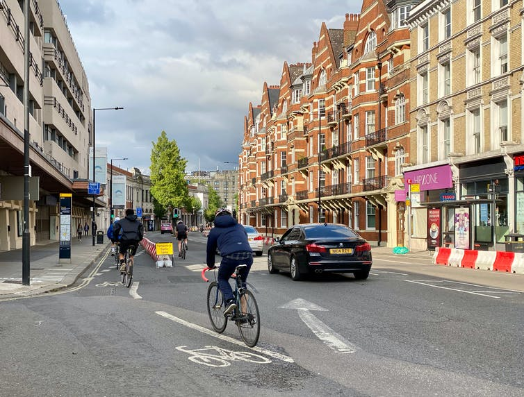 Cyclists pass cars on the left in a temporary cycle lane in Hammersmith, London, UK.