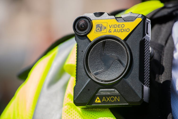 The shoulder of a police officer in the UK with a bodycam on it