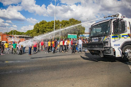 Protesting students standing on the sidewalk looking on at a police truck with a water cannon on the road.