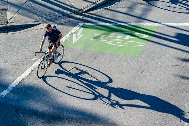 A cyclist crosses an urban intersection.