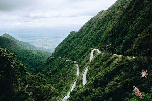 A road winds alongside green mountains