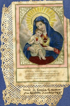 A holy card depicting the Virgin Mary holding infant Jesus with Sacred Heart
