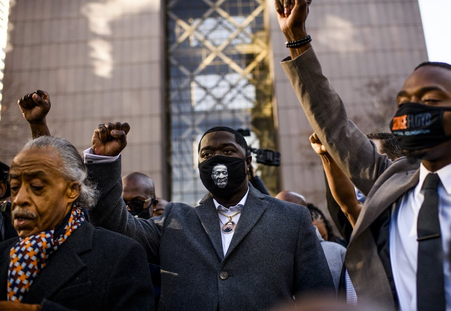 Black men with raised fists outside a court building