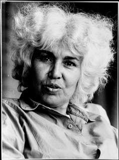 A woman looks directly to camera, her white hair done in dramatic fashion, her lips appear to be talking.