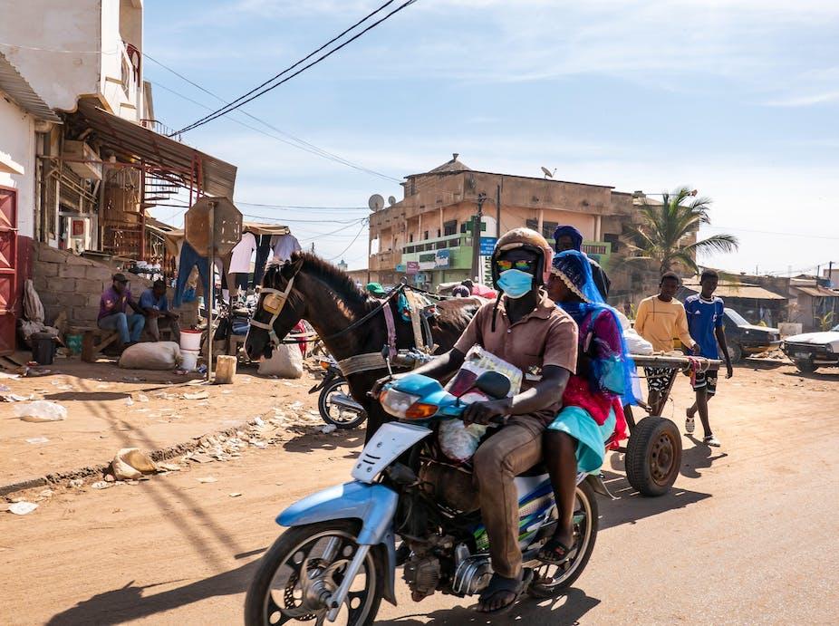 Une scène de rue à Mbour, au Sénégal, avec un homme et une femme sur un scooter et une charrette tirée par un cheval.
