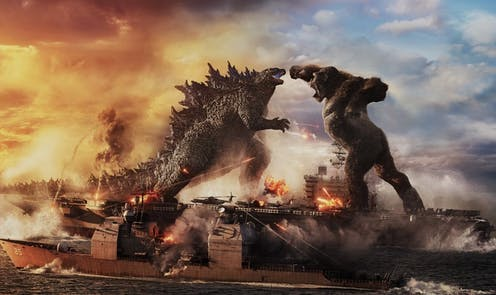 Godzilla and Kong fighting on a large ship.