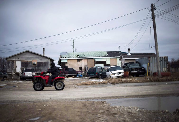 A man rides his ATV through a First Nations community