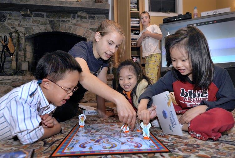 A group of children gather to play Chutes and Ladders on the floor.