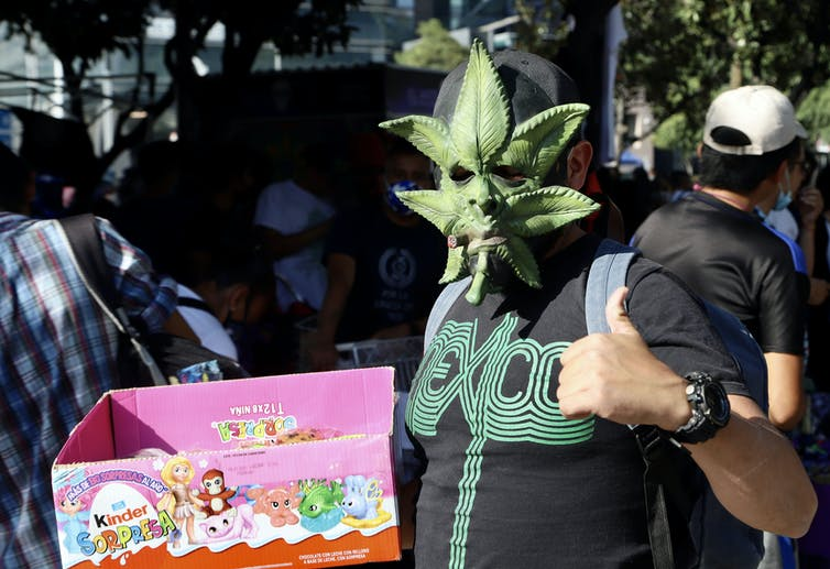 Man holding box of Kinder candies wears a marijuana leaf-shaped mask and gives a thumbs-up