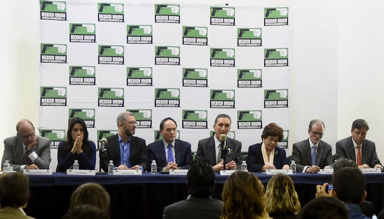 Eight people sit at a long table with microphones; press is visible in the foreground