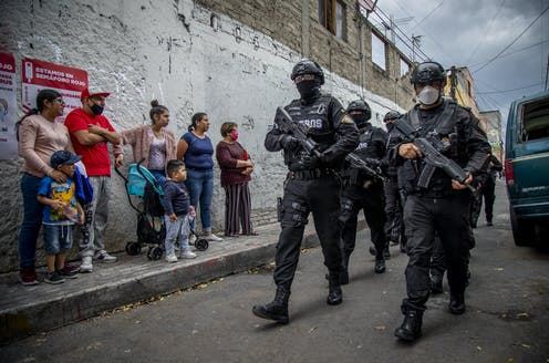 Heavily armed soldiers in full riot gear pass a small crowd of women and children