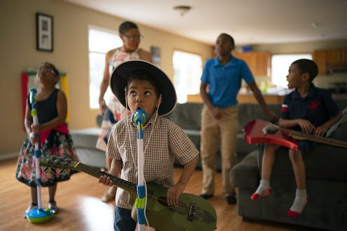 A young Black boy wearing a cowboy hat and holding a guitar sings into a microphone in his living room.