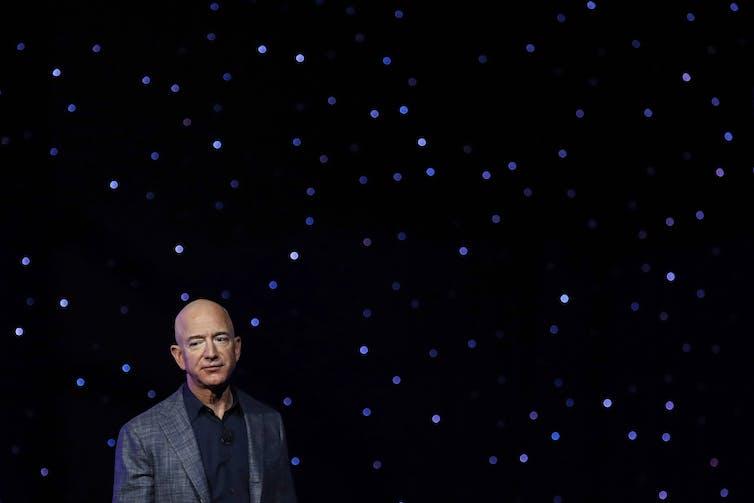 Jeff Bezos stoi na rozgwieżdżonym tle