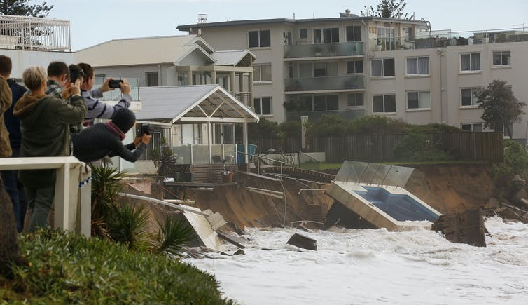 People photograph pool fallen onto beach after storm