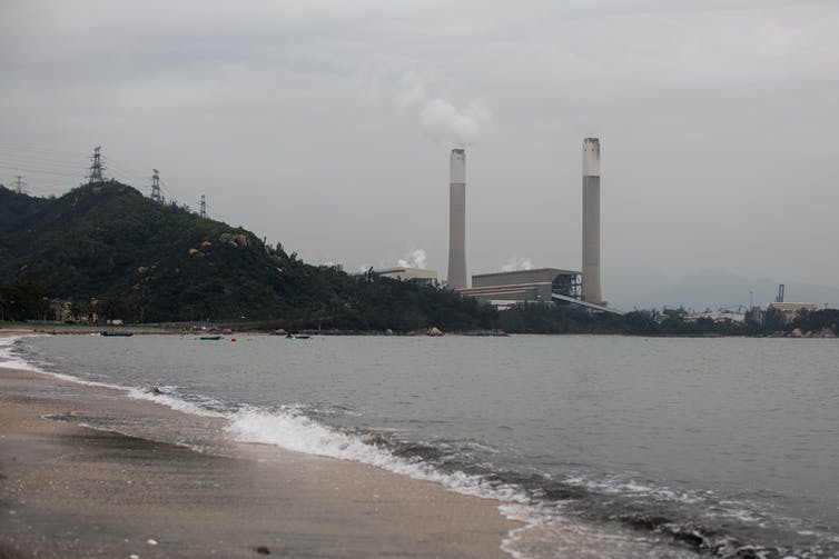 A coal-fired power station belches smoke in a Chinese bay.