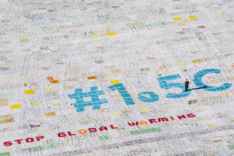 An aerial image of thousands of postcards spelling out '1.5°C stop global warming'.