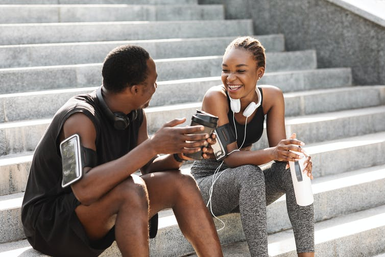 A young man and woman wearing their activewear pause after a workout to drink water and coffee.