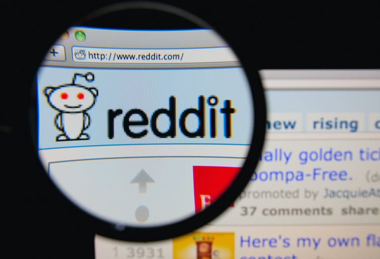 A magnifying glass over the Reddit logo on a web browser