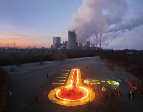 A burning thermometer points to a coal-fired power station in the distance.