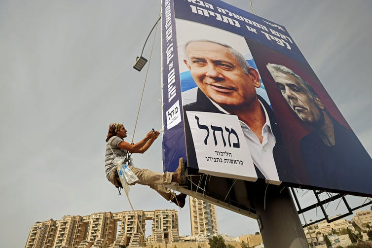 A young man hangs a Likud party election campaign banner, depicting Israeli prime minister Benjamin Netanyahu and his challenger, Yesh Atid party leader, Yair Lapid.