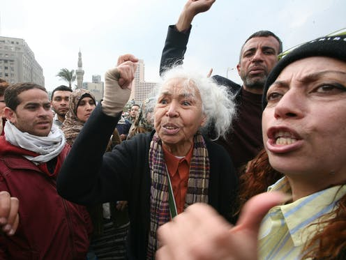 a group of protesters, at their centre a grey-haired woman with her fist raised.