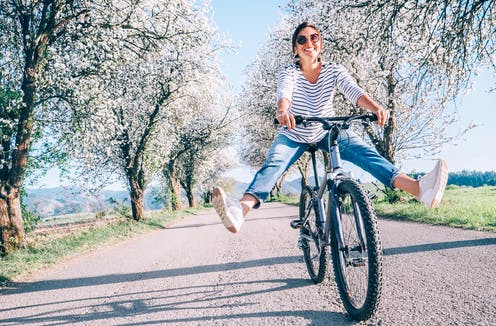 Happy smiling woman on bicycle on the country road under blossom trees.
