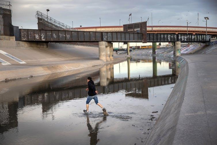 Niño corre a través de un barranco lleno de agua poco profundo