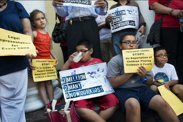 Children hold signs urging the deportation of children to end