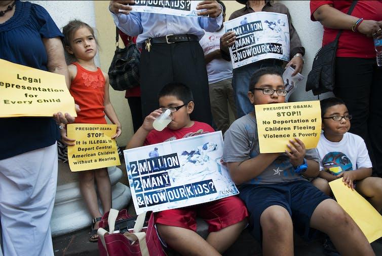 Los niños sostienen carteles instando a que se ponga fin a la deportación de niños
