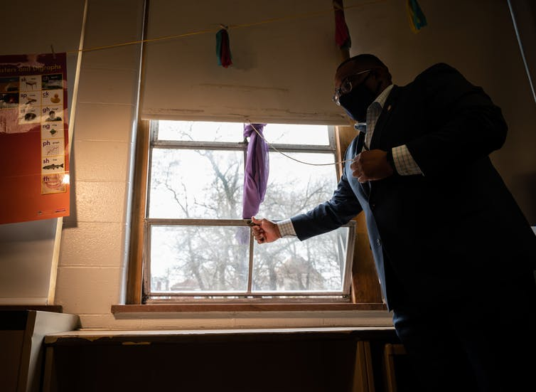 Man in suit opens window of school classroom