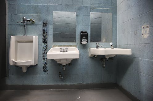 A urinal and two sinks in a rundown public restroom