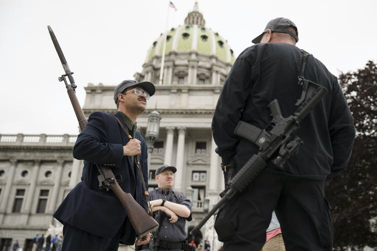 Two men with guns outside the Pennsylvania state capitol