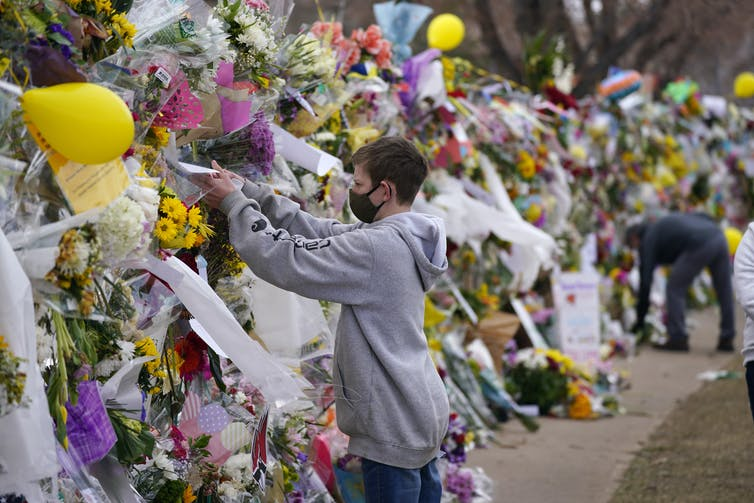 A person places an item in a wall of flowers and messages mourning the victims of the Boulder supermarket shooting.