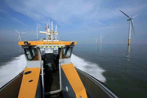 Yellow service boat heads toward offshore wind turbines.