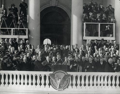 A crowd watches a man on a balcony swear an oath